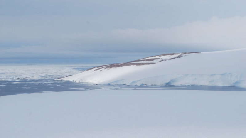 Montanha coberta de gelo à direita. Mar à esquerda.