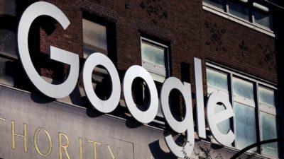 Logo do Google em metal na fachada de um prédio de tijolos marrom.