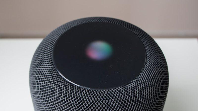 Alto-falante redondo com uma pequena luz colorida no centro da parte superior.