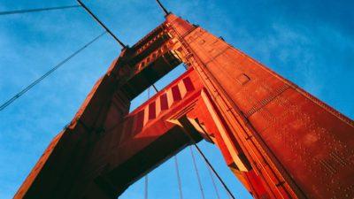 Detalhe da ponte Golden Gate, em San Francisco, Califórnia. Uma torre metálica vermelha se erguendo. Ao fundo, o céu azul.